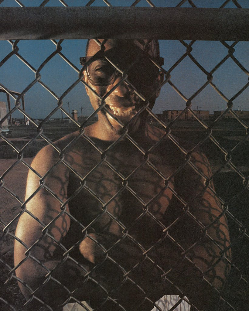 Kevin Hutchinson looks through a chain link fence at prison.